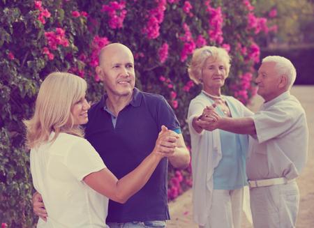Happy aged parents with adult children dancing in summer garden Banco de Imagens - 119563239
