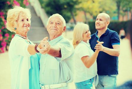 Frohe lächelnde erwachsene Freunde tanzen Paartanz im Garten Standard-Bild