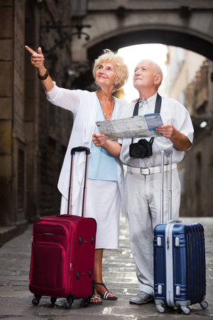 active elderly travellers with suitcases visiting sights of European city with map