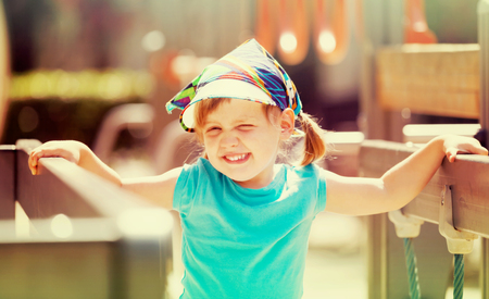 laughing three-year girl at playground area in sunny  day Фото со стока