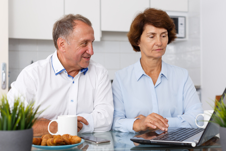 Mature man and woman talking while working at laptop together at home interior
