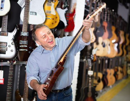 Adult glad cheerful  smiling guitarist is playing on electric guitar in music store.