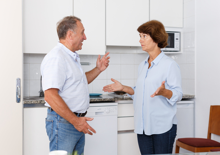 Portrait of sad mature couple discussing, quarrel at home kitchen indoor Banco de Imagens
