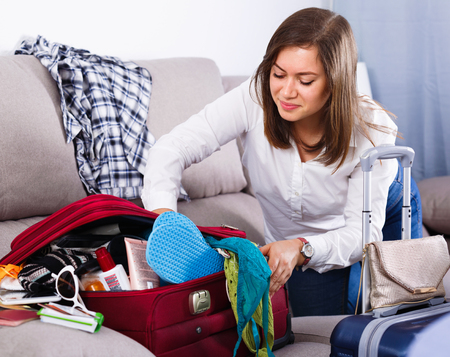Young  cheerful positive girl starting packing luggage for journey at home Stok Fotoğraf
