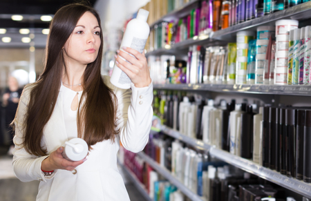 Serious young woman attentively looking hair shampoo at cosmetics store Standard-Bild