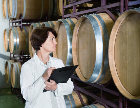 Diligent positive expert examines equipment at winery and writes down remarks