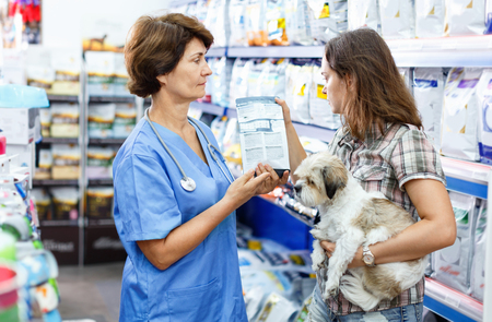 Elderly glad female veterinarian recommending pet food to young woman visiting pet store with her puppy
