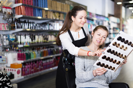 smiling hairdresser edvise woman client about samples of hair dye in beauty showroom Imagens