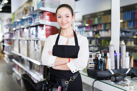 Adult cheerful female hairdresser in apron standing in cosmetics studio
