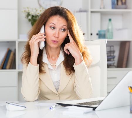 Young office woman is talking about project with partner in the office. Stock Photo