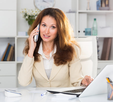 Female is working and talking by phone in the office.