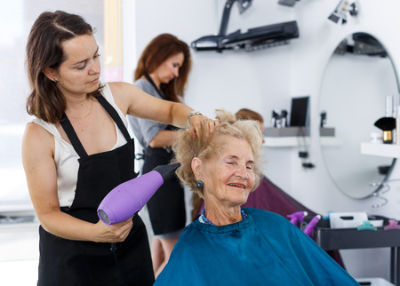 Professional female stylist making hairdo for senior woman in salon, using hair dryer
