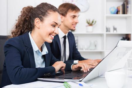 Friendly diligent business female assistant wearing formalwear using laptop in company office