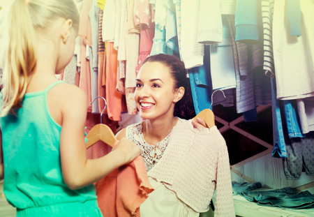 smiling young woman selecting pink dress for her little  daughter  in children clothes store Stock Photo