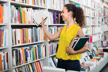Young glad woman holding books in hard cover in bookstore