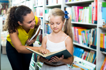 Happy woman showing open book to girl in school age in book boutique Stock Photo
