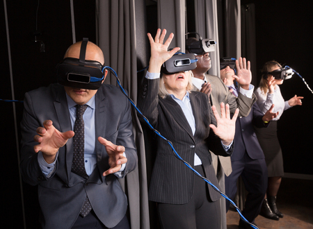 Excited adult man in business suit having fun with his friends in virtual reality room