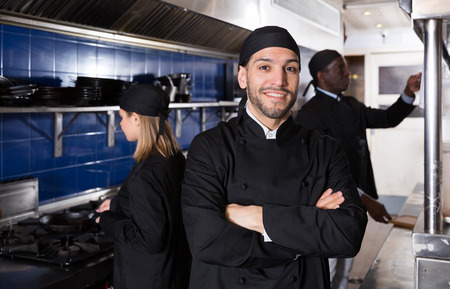 Confident chef of restaurant posing with arms crossed in kitchen on background with employees 写真素材