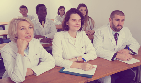 Group of physicians of different nationalities during seminar in conference room Standard-Bild - 119683663