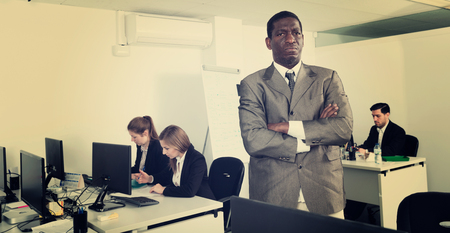 Confident African American diligent businessman standing with arms crossed in busy modern open plan office