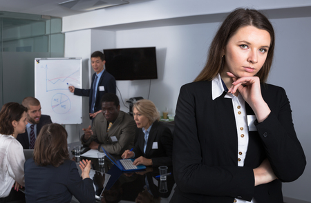 Business team discussing in meeting room with thoughtful young woman foreground Standard-Bild - 119683665