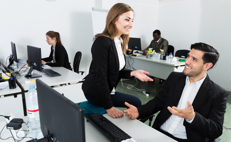 Positive young business woman flirting with man working at laptop in coworking