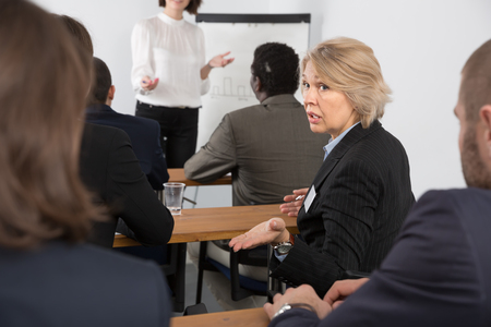 Discontent senior woman turning to other participants during business presentation Standard-Bild - 119683672