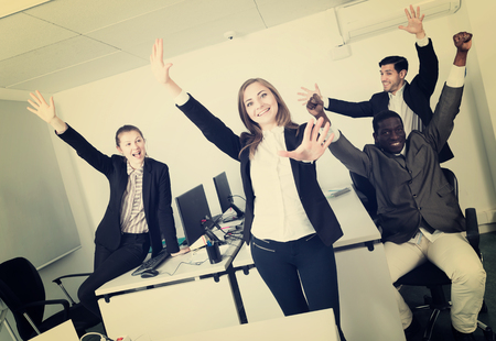 Satisfied international  workgroup expressing satisfaction with teamwork at office, enjoying and  hands up Stock Photo
