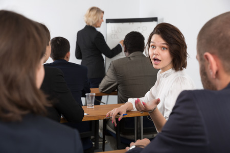 Young emotional woman turning to other participants during business training in meeting room Standard-Bild - 119684715