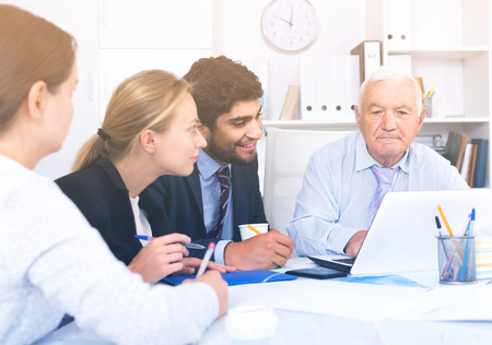 Employees are working together at computer in the office. Stock Photo