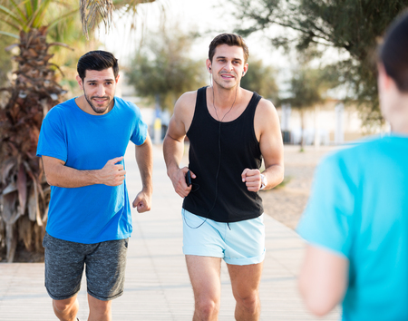 Adult men are jogging together in the park near ocean.