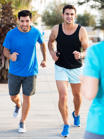 Two smiling sportsmen are jogging in time training in the park near ocean 스톡 콘텐츠