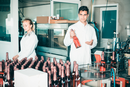 Happy man holding bottle of wine in packing  section of wine factory Фото со стока