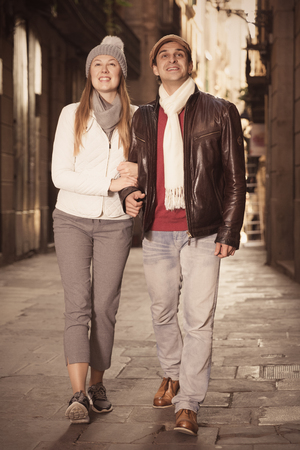 Positive male and female walking in the historic center in autumn
