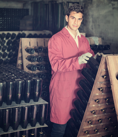 Attentive diligent  man winery employee wearing coat working in aging section with bottle racks in cellar