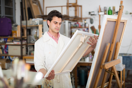 Smiling man with brush near easel painting on canvas