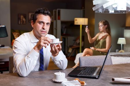 Focused man drinking coffee and working with laptop at home with young woman in blurred background