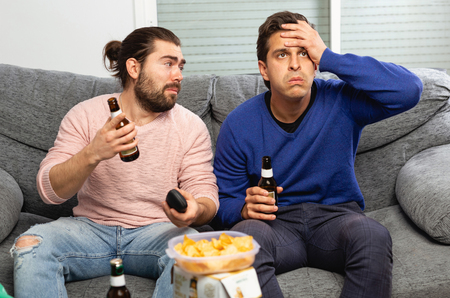 Two men watching matchup on tv drinking beer together at home Stock Photo