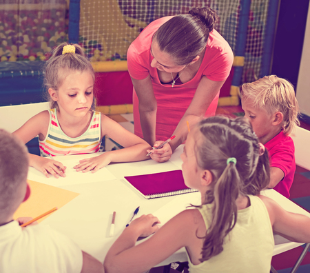 Careful girls and boys drawing pencils on lesson in elementary school class with help of teacher