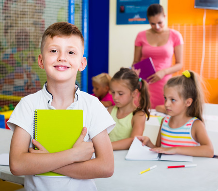 Glad boy pupil standing in elementary school class with textbook in hands