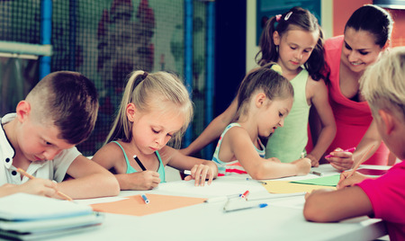 Happy children drawing on lesson in elementary education class with help of teacher