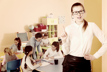 Portrait of positive woman teacher in glasses and boys and girls in classroom