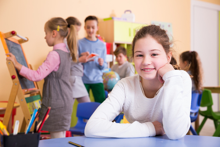 Portrait of smiling schoolgirl sitting at table in classroom relaxing during break