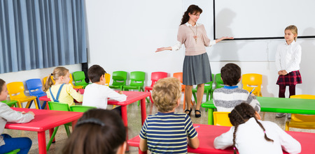 Portrait of friendly female teacher standing near whiteboard with schoolgirl during lesson in classroom