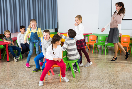 Happy laughing pupils of primary school having fun during break with their teacher, playing musical chairs Stock Photo