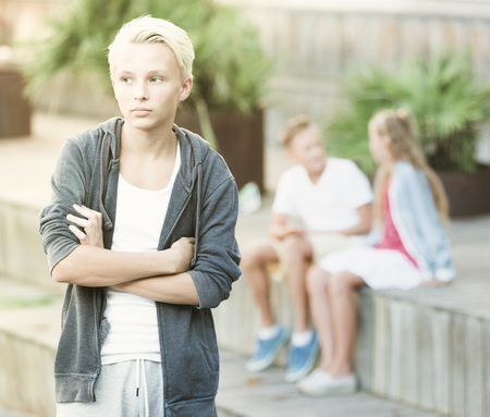 Portrait of offended boy not talking with friends after quarrel outdoors