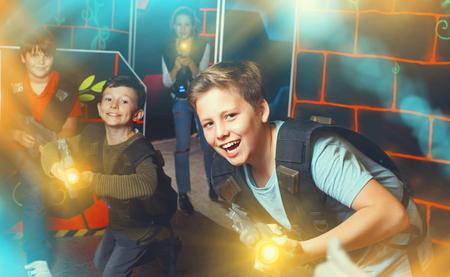 Portrait of happy cheerful preteen boy with laser gun having fun on dark lasertag arena