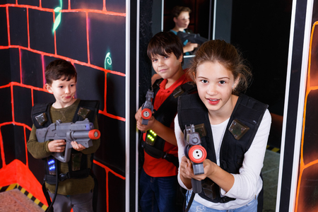 Portrait of happy  positive smiling teenager girl with laser gun having fun on dark lasertag arena 免版税图像
