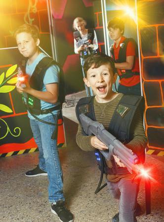 Portrait of  cheerful  smiling preteen boy with laser gun having fun on dark lasertag arena
