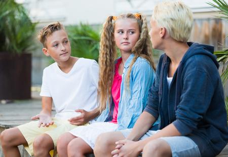 Lächelndes Mädchen mit zwei Jungen, die Diskussion im Freien haben Standard-Bild